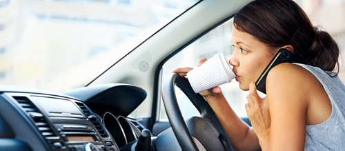 Woman talking on the phone and drinking coffee while driving car