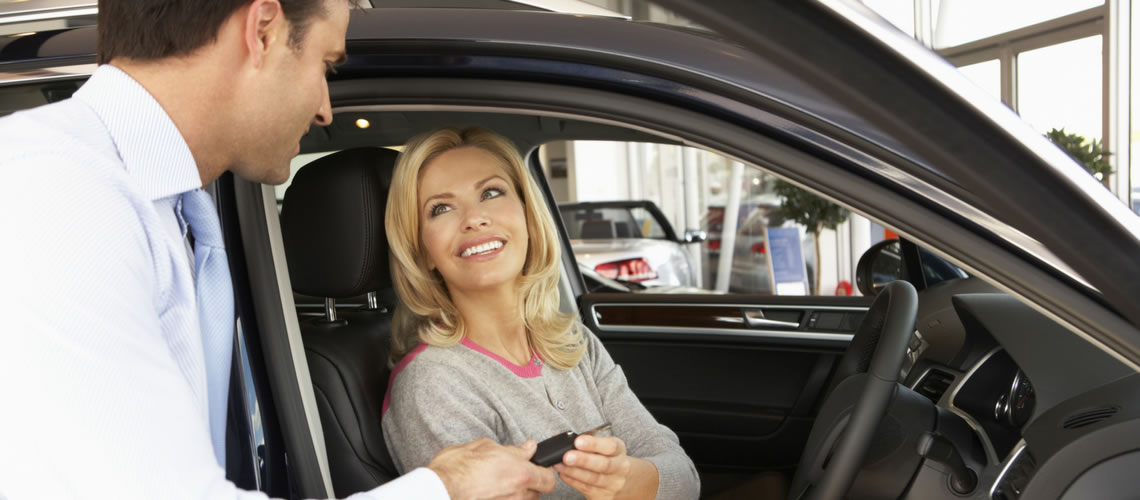 man handing woman keys to new car