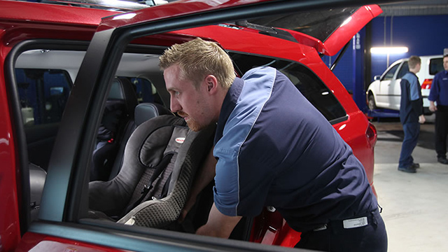 Child seat installation by an NRMA car servicing mechanic