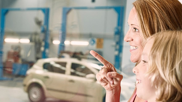 car servicing locations woman pointing with child in mechanics