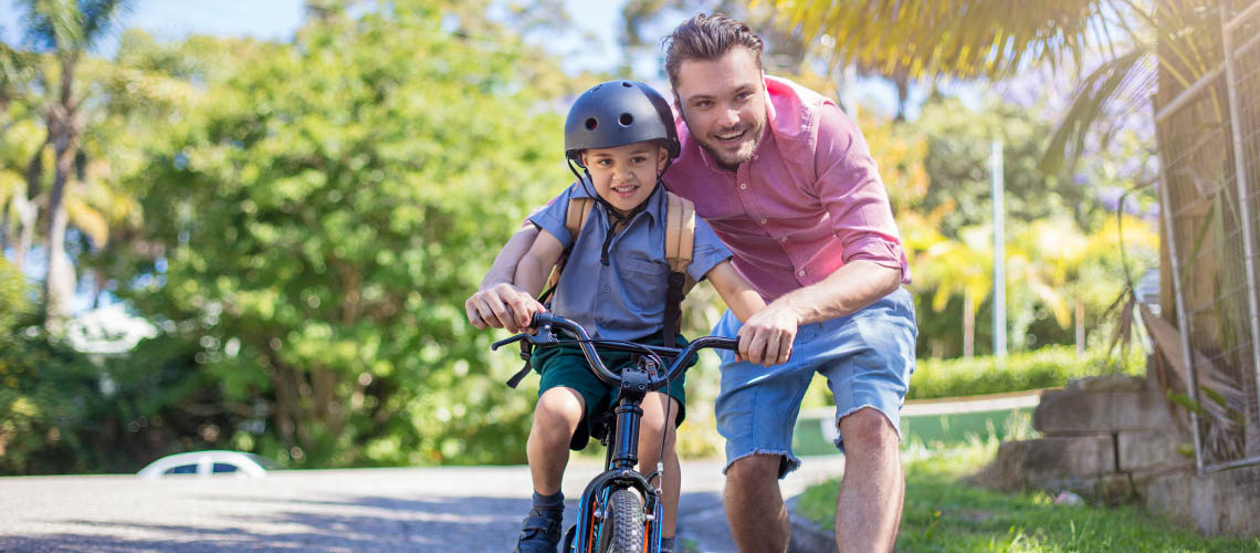 Father teaching son how to ride bicycle | Motoring education