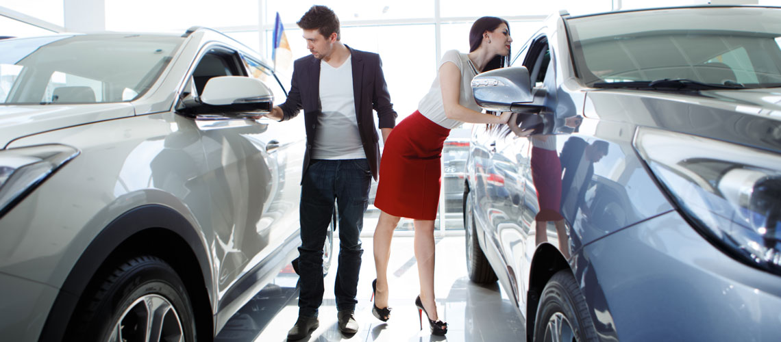Young-couple-looking-at-new-cars