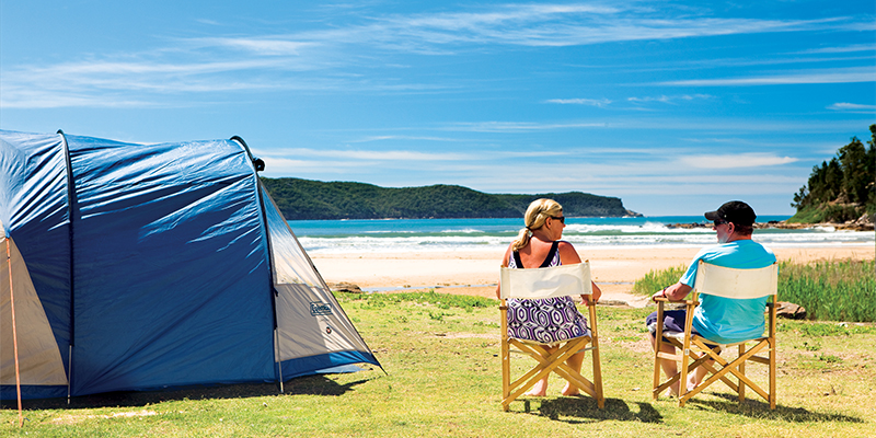 Couple relaxing near tent my nrma road trips Ocean Beach Holiday Resort