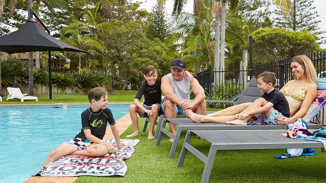 family relaxing poolside Port Macquarie Breakwall Holiday Park NSW my nrma local guides