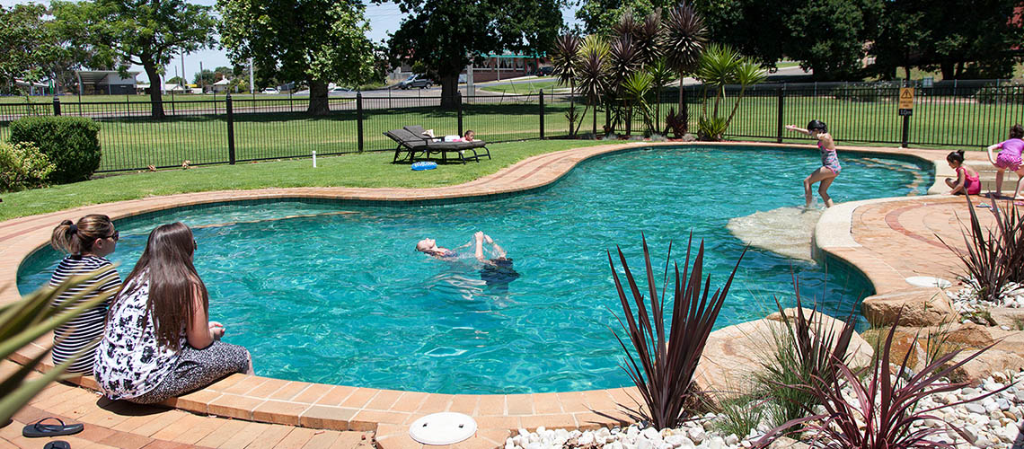 family relaxing poolside Bairnsdale Riverside Holiday Park Victoria my nrma local guides