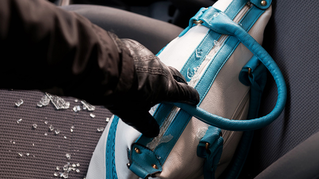 car break in robber grabbing handbag with glass shattered