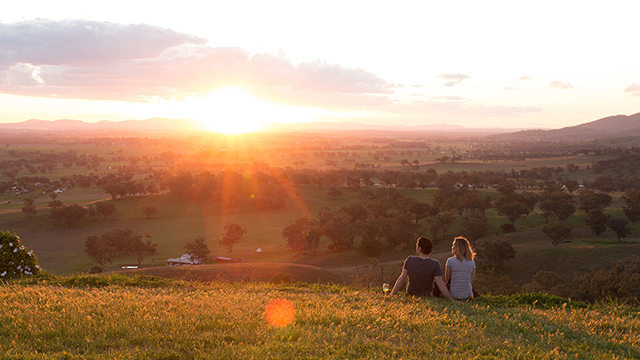 Couple enjoying a glass of wine at sunset in Tamworths countryside #newsouthwales