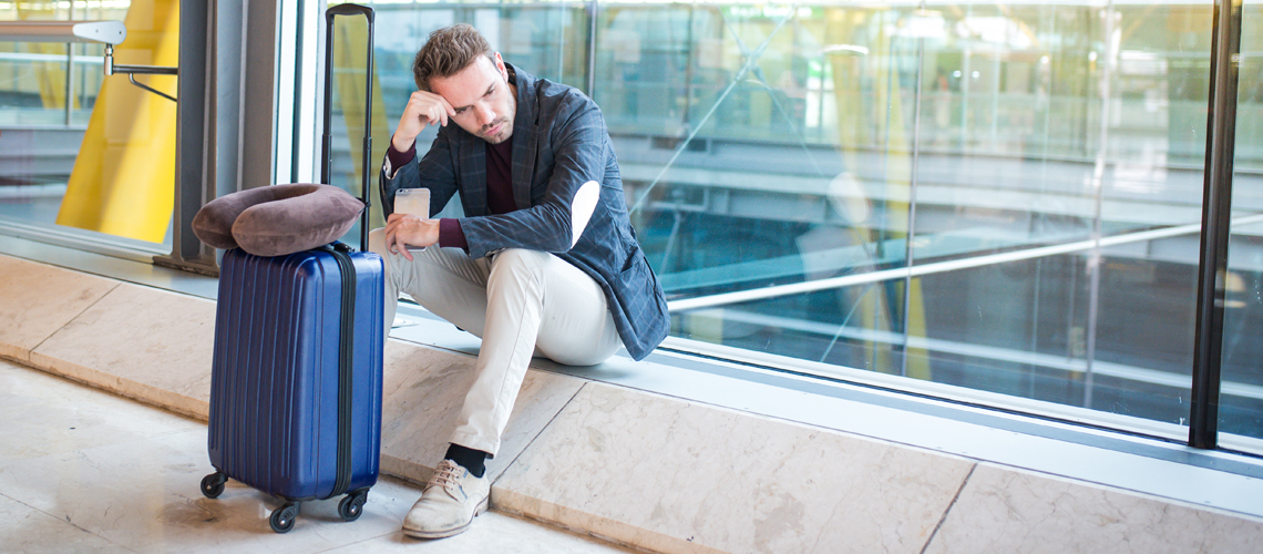 Man waiting with luggage at airport